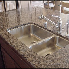 Kitchen island has a marble counter top with Kohler sink and faucet.