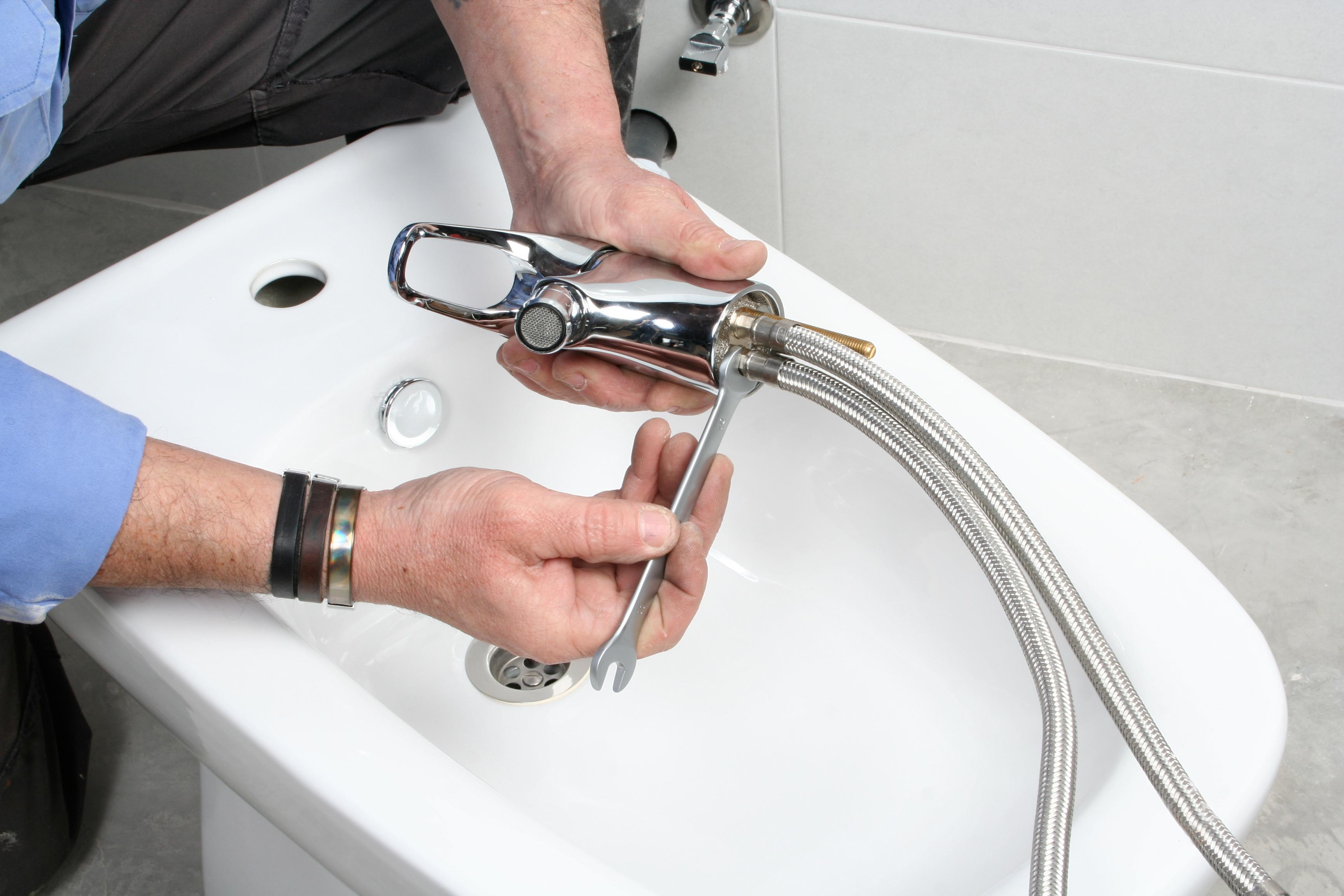 Plumber installing faucet on bidet in bathroom