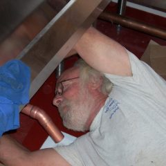 LeDuc & Dexter plumber installing drain pipe under bar.