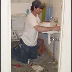 Crew setting new sink into place during bathroom remodel.